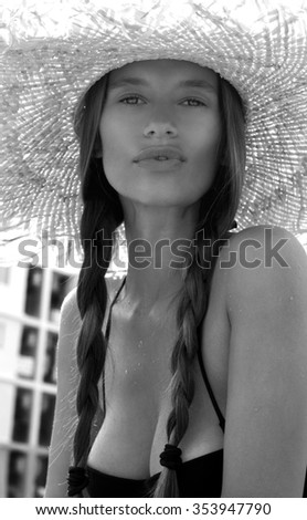 Woman in hat and black stylish swimsuit with pigtails poses on roof enjoying landscape view. Phuket island, Thailand. High fashion look.