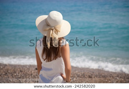 Woman in hat and elegant white dress near the sea on a summer day. Enjoying looking view of beach sea on hot summer day. Travel holidays vacation  - stock photo