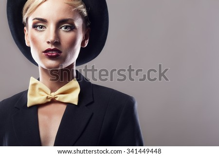 Woman in hat and yellow bow on grey background in studio photo. Art and sensuality. Isolated over background. Perfect fashion