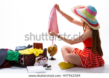 Woman in hat beside suitcase. Girl holds piece of clothing. This one is too small. Too much clothes in luggage. - stock photo