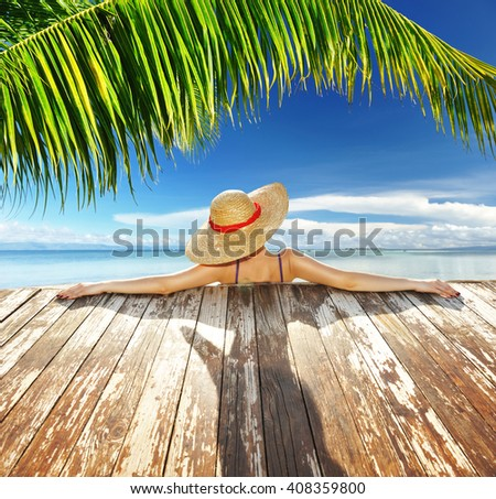Woman in hat relaxing at beach jetty - stock photo