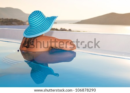 Woman in hat relaxing at swimming pool in Greece - stock photo