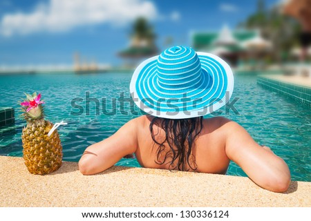 Woman in hat relaxing at swimming pool in Thailand - stock photo