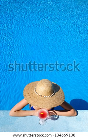 Woman in hat relaxing at the pool with cosmopolitan cocktail - stock photo