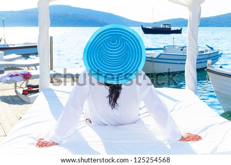 Woman in hat relaxing on luxury white bed at the sea - stock photo