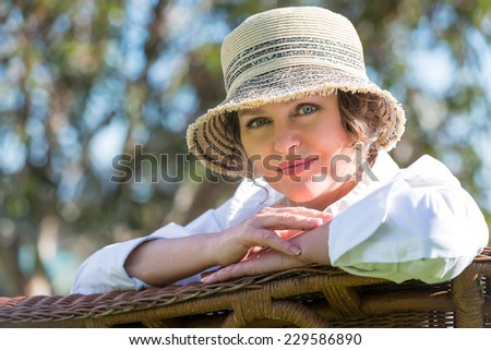 Woman in hat  sitting on a wicker bench in the garden - stock photo