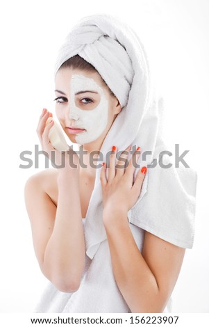 Woman in headband with lifting cream applied on a half of her face take soap, isolated on white