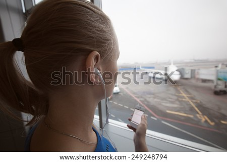Woman in headphones by the window at aiport listening to music using smart phone. Entertainment during flight waiting