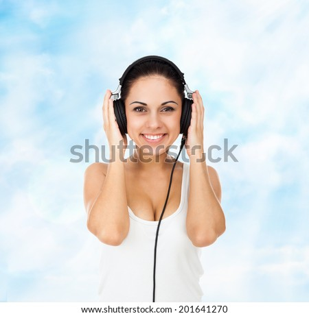 woman in headphones listen to music smile over blue sky cloud background