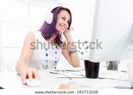 Woman in headphones sitting at desk in office - stock photo