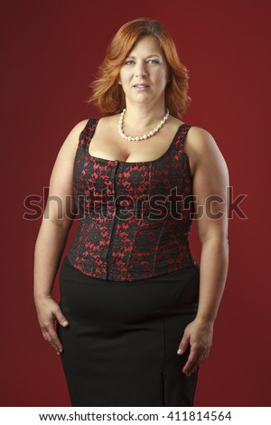 Woman in her forties wearing a red corset - stock photo