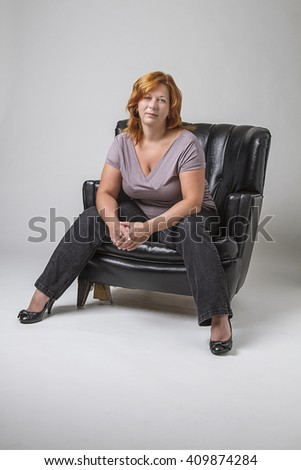 woman in her forty with red hair sitting on a black leather love set - stock photo