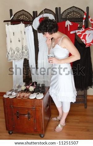 Woman in her 30s-40s standing next to a collection of shoes and other hanging clothes - thinking