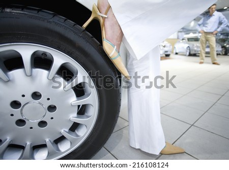 Woman in high heels leaning on new car - stock photo