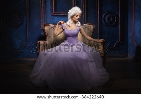 Woman in historic baroque style dress and white wig in a luxury interior