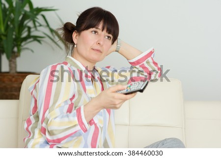 Woman in home watching television and changing channels with remote control