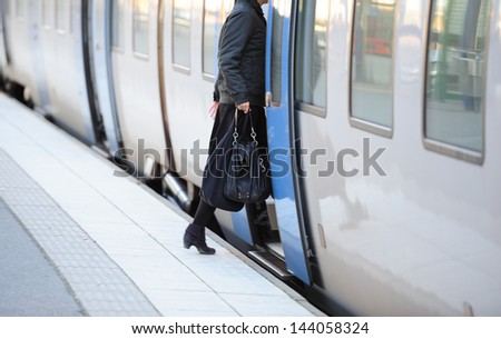 Woman in hurry enters train - stock photo