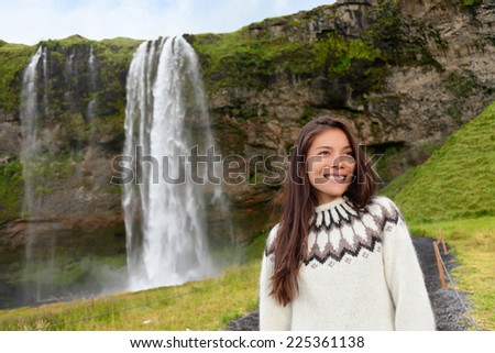Woman in Icelandic sweater by waterfall on Iceland outdoor smiling. Portrait of beautiful female model in nature landscape with tourist attraction Seljalandsfoss waterfall on Ring Road. - stock photo