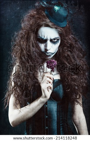 Woman in image of a gothic freak clown with withered flower. Grunge texture effect  - stock photo