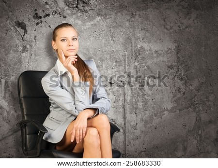 Woman in jacket and blouse sits on chair. Background of concrete wall - stock photo