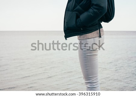 Woman in jeans and a jacket standing on a sea background. Walking along the beach in the fall.