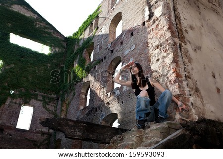 Woman in jeans in a deserted building looking to see if there is somebody coming.