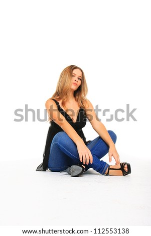 Woman in jeans sitting on the floor isolated on white - stock photo