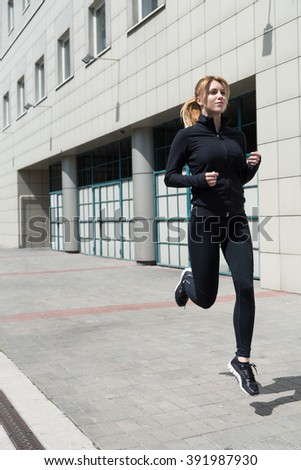 Woman in jogging tracksuit training for the marathon - stock photo