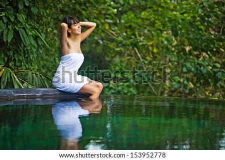 woman in jungle spa near swimming pool - stock photo