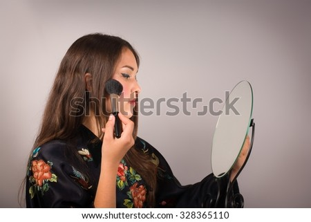 woman in kimono prepares herself in front of a mirror - stock photo