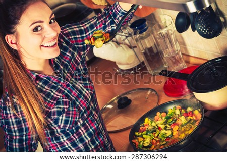 Woman in kitchen cooking stir fry frozen vegetables and tasting. Girl frying making delicious dinner food meal. Instagram filtered. - stock photo
