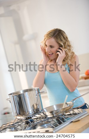 woman in kitchen cooking while making a cell phone - stock photo