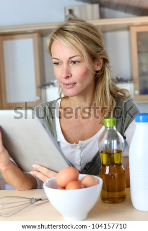 Woman in kitchen looking at dessert recipe on internet - stock photo