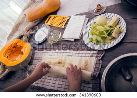 Woman in kitchen making prepares a pie with pumpkin - stock photo