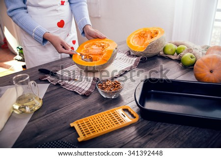 Woman in kitchen making prepares a pie with pumpkin, selective focus - stock photo