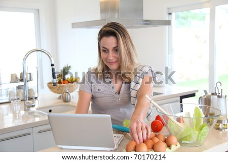 Woman in kitchen preparing lunch - stock photo