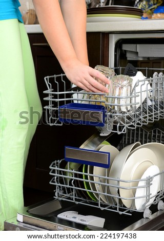 woman in kitchen using dishwasher