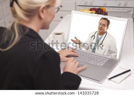 Woman In Kitchen Using Laptop - Online Chat with Nurse or Doctor on Screen. - stock photo