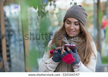 Woman in knitted garment, cap and gloves dials the phone number in city.