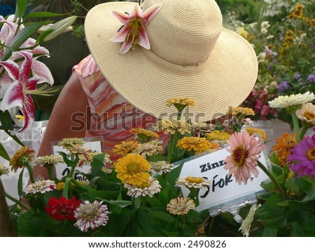 Woman in large hat in outdoor flower stand