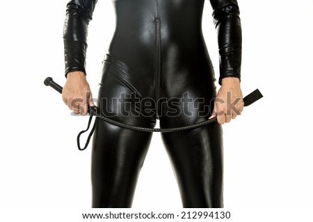 Woman in latex suit holding a leather whip - stock photo