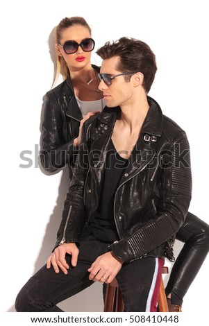 woman in leather jacket is looking at her seated man , both wear sunglasses in studio