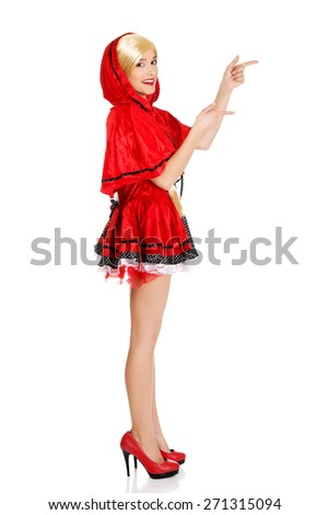 Woman in Little Red Riding Hood costume pointing aside. - stock photo