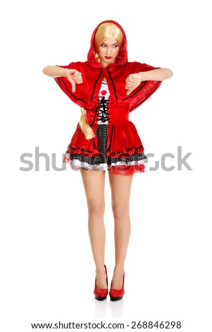 Woman in Little Red Riding Hood costume with thumbs down. - stock photo