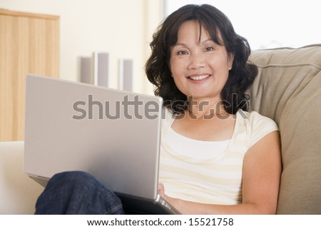 Woman in living room using laptop and smiling