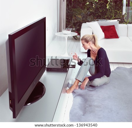Woman in living room watching home cinema - stock photo