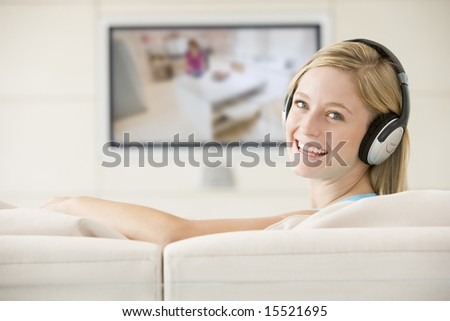 Woman in living room watching television smiling - stock photo