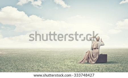 Woman in long dress and hat sitting on retro suitcase