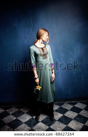 woman in long dress stand in empty room hold orchid in one hand - stock photo