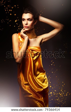 woman in long yellow dress and jewelry - stock photo